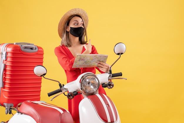 Vue de face jeune femme avec masque noir tenant une carte près d'un cyclomoteur