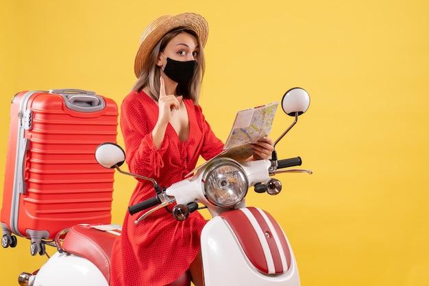 Vue de face jeune femme avec masque noir tenant une carte surprenante avec une idée près d'un cyclomoteur