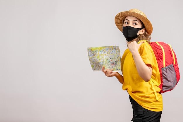 Vue de face jeune femme avec masque noir tenant la carte