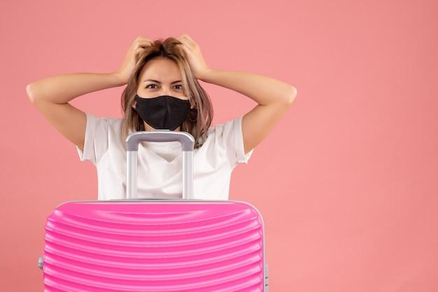 Vue de face jeune femme avec masque noir tenant sa tête derrière une valise rose