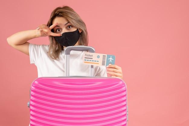 Vue de face jeune femme avec masque noir tenant un ticket debout derrière une valise rose