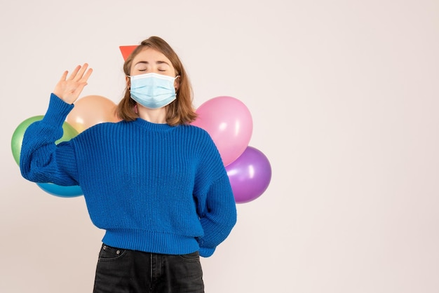 Vue de face jeune femme en masque stérile cachant des ballons colorés derrière son dos