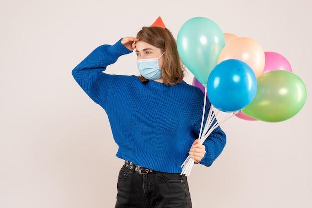 Vue de face jeune femme en masque stérile tenant des ballons colorés