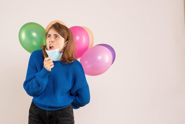 Vue de face jeune femme en masque tenant des ballons colorés derrière son dos