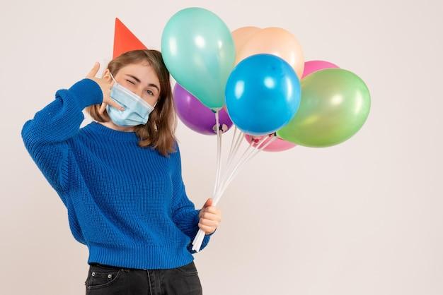 Vue de face jeune femme en masque tenant des ballons colorés