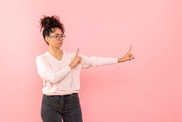 Vue de face de la jeune femme mécontente sur mur rose