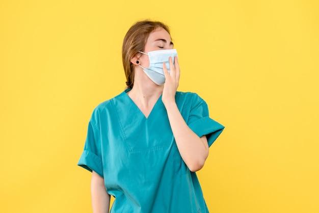 Vue de face de la jeune femme médecin bâillement