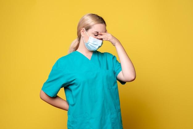 Vue de face de la jeune femme médecin en chemise médicale et masque stérile stressé sur le mur jaune