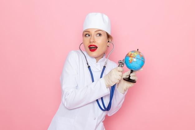 Vue de face jeune femme médecin en costume médical blanc avec stéthoscope bleu contrôle petit globe sur l'hôpital médical de médecine de l'espace rose