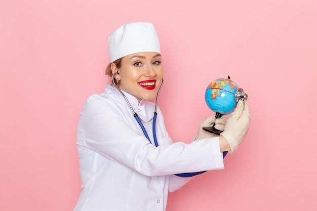Vue de face jeune femme médecin en costume médical blanc avec stéthoscope bleu contrôle petit globe souriant sur l'hôpital médical de médecine de l'espace rose