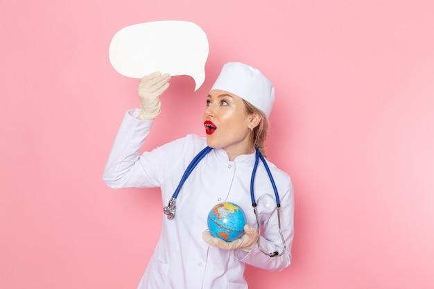 Vue de face jeune femme médecin en costume médical blanc avec stéthoscope bleu tenant petit globe sur la santé de l'hôpital médical médecine de l'espace rose