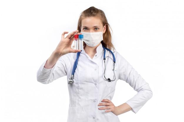 Une vue de face jeune femme médecin en costume médical blanc avec stéthoscope portant un masque de protection blanc posant tenant des flacons sur le blanc