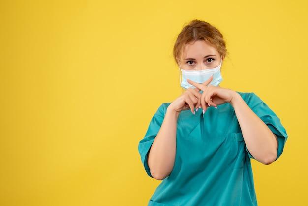 Vue de face de la jeune femme médecin en costume médical et masque stérile sur mur jaune