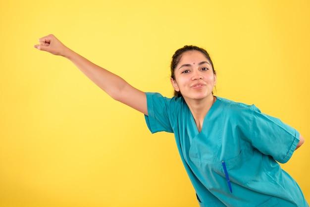 Vue de face de la jeune femme médecin en héros volant pose sur mur jaune