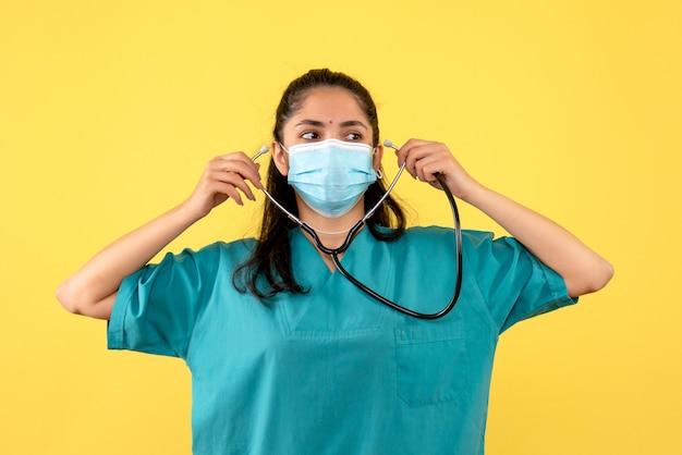 Vue de face jeune femme médecin avec masque médical à l'aide d'un stéthoscope debout sur fond jaune