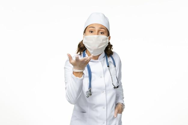 Vue de face jeune femme médecin avec masque stérile et gants de protection en raison d'un coronavirus sur un bureau blanc