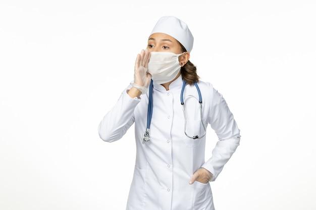 Vue de face jeune femme médecin avec masque stérile et gants en raison du coronavirus chuchotant sur une surface blanche