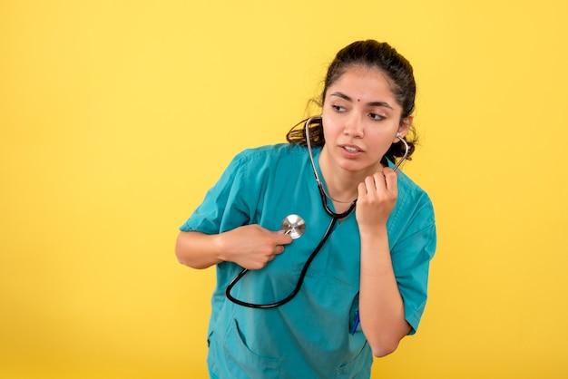 Vue de face de la jeune femme médecin mettant le stéthoscope sur son cœur sur le mur jaune