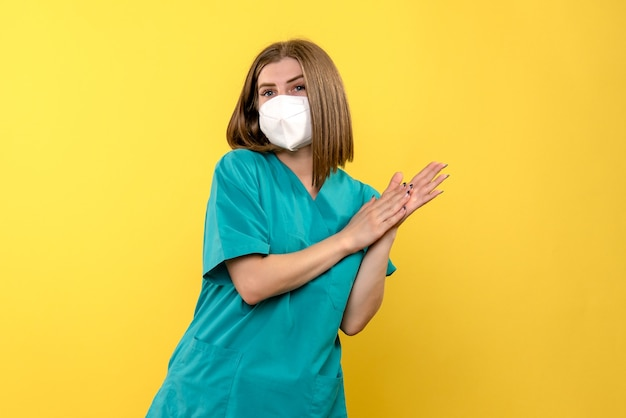 Vue de face de la jeune femme médecin sur mur jaune