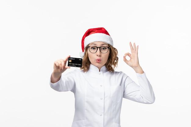 Vue de face jeune femme médecin tenant la carte bancaire sur le bureau blanc argent infirmière nouvel an