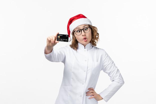 Vue de face jeune femme médecin tenant une carte bancaire sur fond blanc vacances infirmière nouvel an