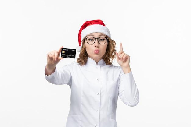 Vue de face jeune femme médecin tenant une carte bancaire sur le mur blanc de l'argent nouvel an