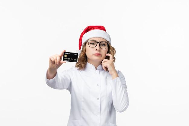 Vue de face jeune femme médecin tenant une carte bancaire sur un mur blanc nouvelle année infirmière