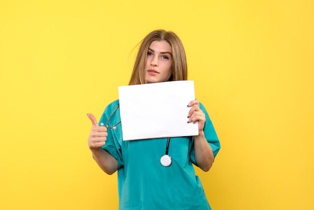 Vue de face de la jeune femme médecin tenant des fichiers sur l'hôpital médical de maladie de plancher jaune