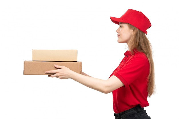 Une vue de face jeune femme de messagerie femme ouvrière du service de livraison de nourriture souriant boîtes de délissage avec de la nourriture sur blanc