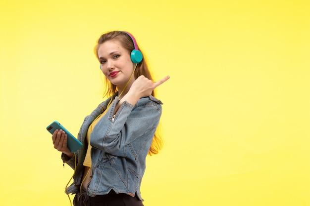 Une vue de face jeune femme moderne en chemise jaune pantalon noir et manteau en jean avec des écouteurs colorés à l'aide de téléphone posant