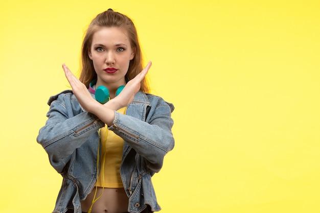 Une vue de face jeune femme moderne en chemise jaune pantalon noir et manteau en jean avec des écouteurs colorés écouter de la musique posant montrant signe d'interdiction