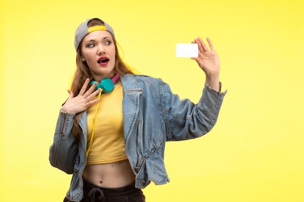 Une vue de face jeune femme moderne en chemise jaune pantalon noir et manteau en jean avec des écouteurs colorés tenant une carte blanche posant