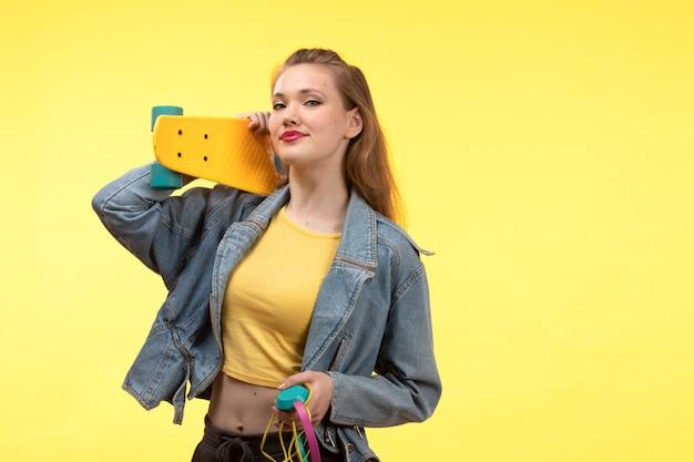 Une vue de face jeune femme moderne en chemise jaune pantalon noir et manteau en jean tenant une planche à roulettes avec des écouteurs colorés