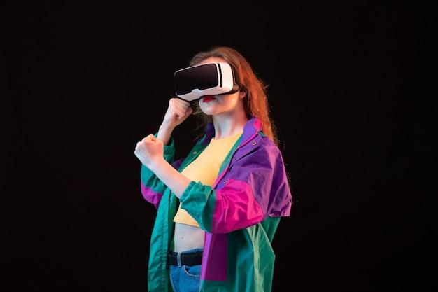Une vue de face jeune femme moderne en manteau coloré orange t-shirt jouant et essayant des expressions mains vr se déplace sur le fond noir jeu interactif