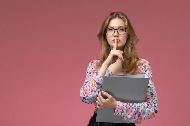 Vue de face jeune femme montrant le geste de silence avec son document