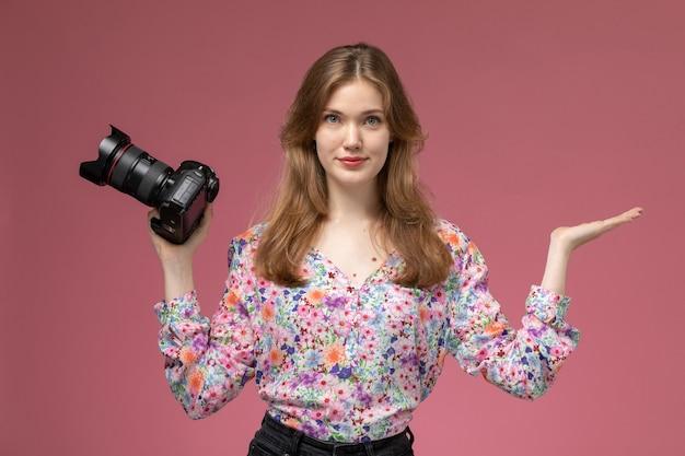 Vue de face jeune femme montrant la main vide et photocamera