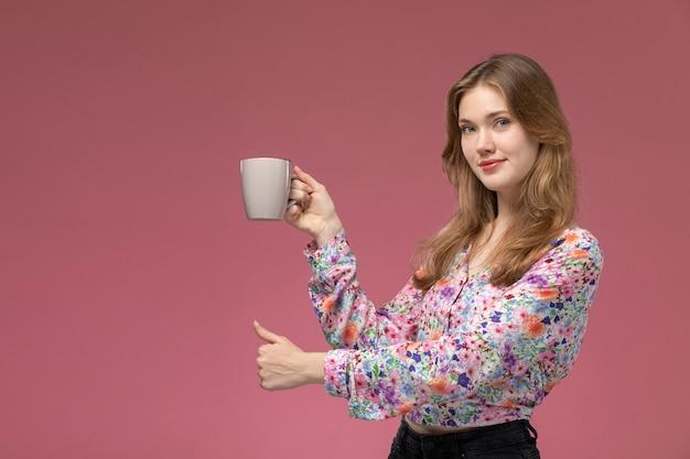 Vue de face jeune femme montre qu'elle aime sa tasse