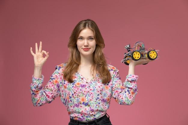 Vue de face jeune femme montre qu'il aime les jouets de voiture