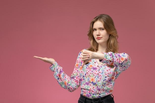 Vue de face jeune femme n'aimait pas quelque chose sur le mur rose