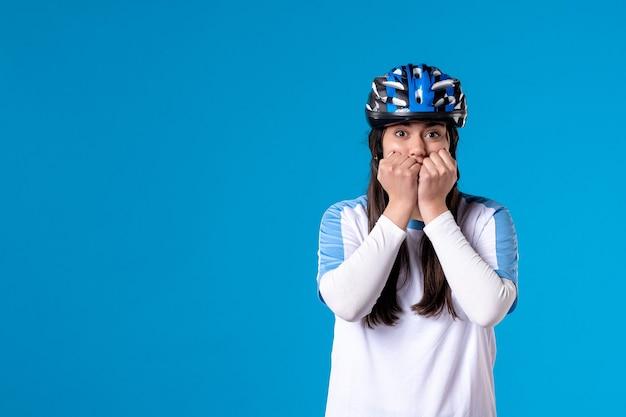 Vue de face jeune femme nerveuse en vêtements de sport et casque sur bleu