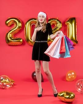Vue de face jeune femme en noir mettant la main sur sa robe de poitrine tenant des sacs à provisions des ballons sur rouge