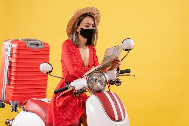 Vue de face d'une jeune femme occupée avec un masque noir en regardant la carte près de cyclomoteur