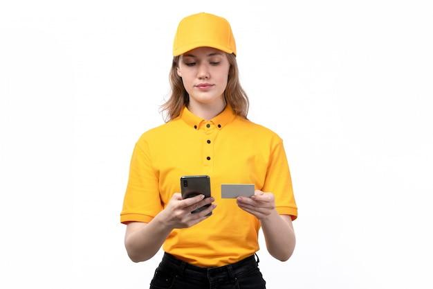 Une vue de face jeune femme ouvrière de messagerie du service de livraison de nourriture entrant les informations de la carte blanche dans le téléphone sur blanc
