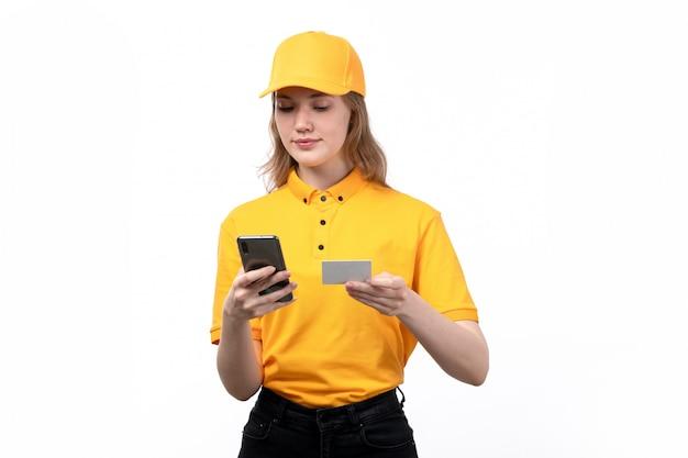 Une vue de face jeune femme ouvrière de messagerie du service de livraison de nourriture souriant tout en tapant des informations de carte blanche dans le téléphone sur blanc