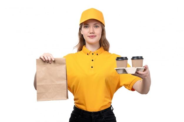 Une vue de face jeune femme ouvrière de messagerie de service de livraison de nourriture souriant tenant le paquet de nourriture et tasses à café sur blanc