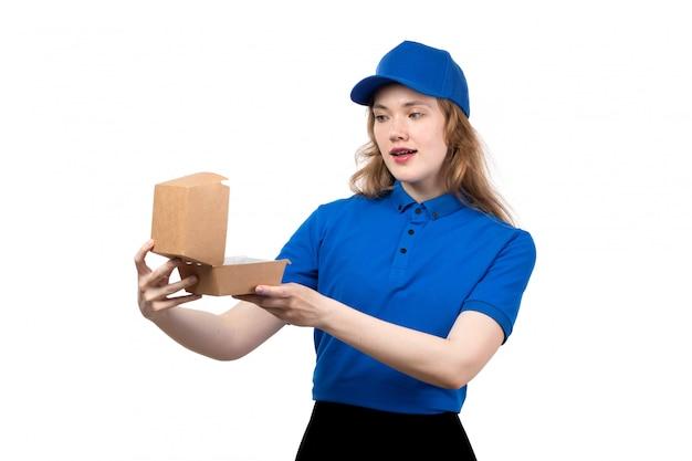 Une vue de face jeune femme ouvrière de messagerie de service de livraison de nourriture tenant une boîte de nourriture vide sur blanc