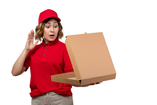 Une vue de face jeune femme ouvrière de messagerie de service de livraison de nourriture tenant une boîte à pizza vide sur blanc