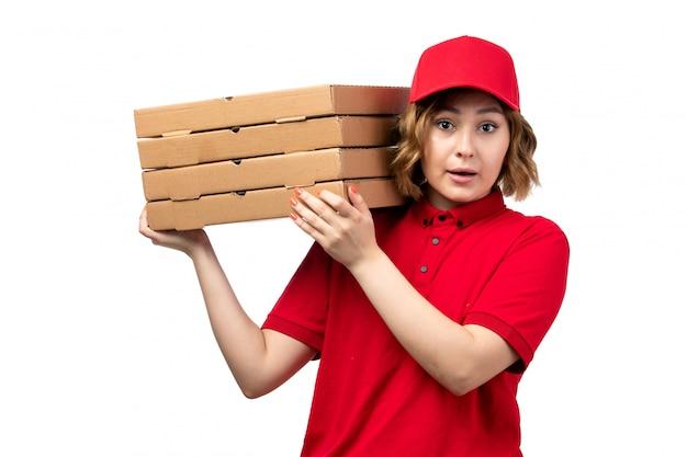 Une vue de face jeune femme ouvrière de messagerie de service de livraison de nourriture tenant des boîtes à pizza sur blanc