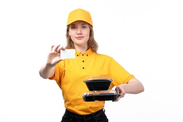 Une vue de face jeune femme ouvrière de messagerie de service de livraison de nourriture tenant une carte blanche et bols avec de la nourriture sur blanc