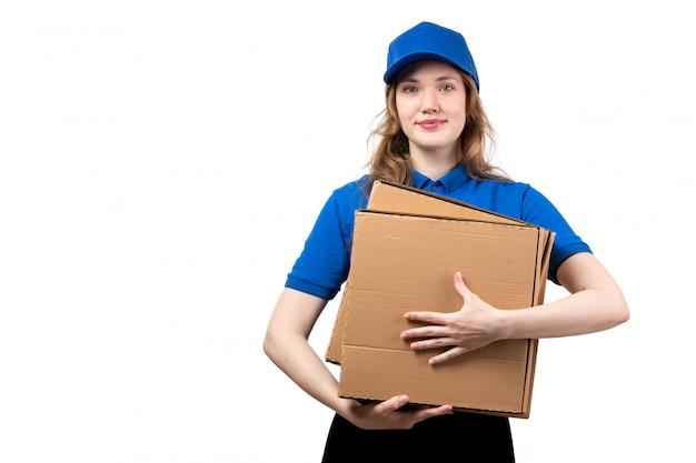 Une vue de face jeune femme ouvrière de messagerie de service de livraison de nourriture tenant des colis de livraison sur fond blanc service uniforme offrant des emplois